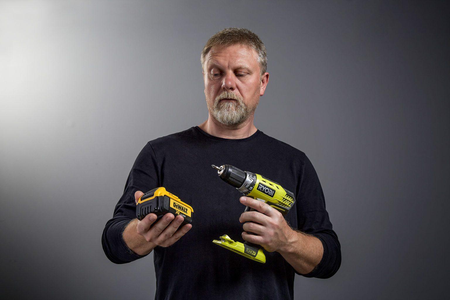 Man staring at DeWalt battery and Ryobi drill